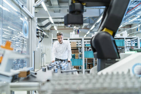 Businessman in a modern factory hall looking at robot - DIGF07310