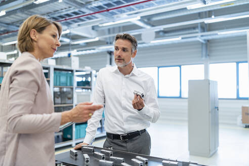 Businessman and businesswoman talking in a modern factory hall - DIGF07319