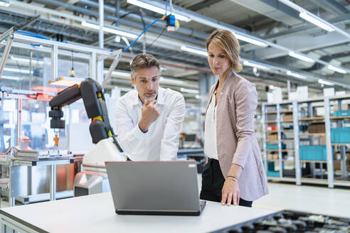 Businessman and businesswoman with laptop talking in a modern factory hall - DIGF07340