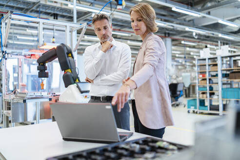 Businessman and businesswoman with laptop talking in a modern factory hall - DIGF07343