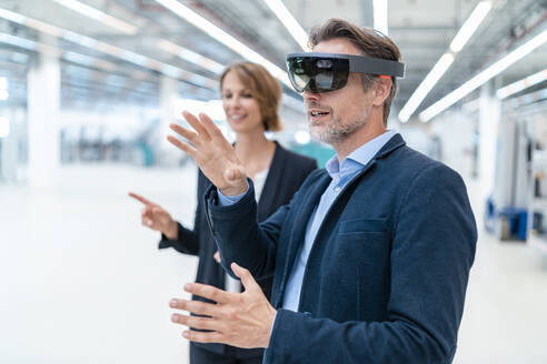 Businessman with AR glasses and businesswoman in a factory hall - DIGF07364