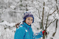 Smiling girl shaking a snowy tree - OGF00018