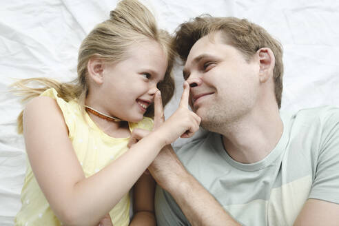 Russia, Sochi, Father and smiling daughter in the bedroom - EYAF00282
