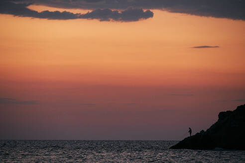 Silhouette of person fishing in sea at sunrise - BZF00494