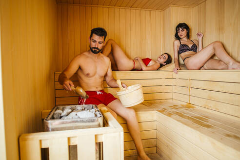 Women and man sitting in a sauna - LJF00414