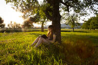 Little girl leaning against tree trunk at sunset reading a book - LVF08163