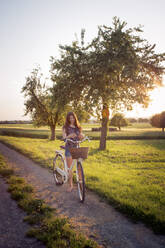 Teenage girl standing next to bike on dirt road at sunset - LVF08167