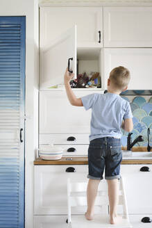 Russia, Moscow, a boy staying on the chair in the kitchen - EYAF00289