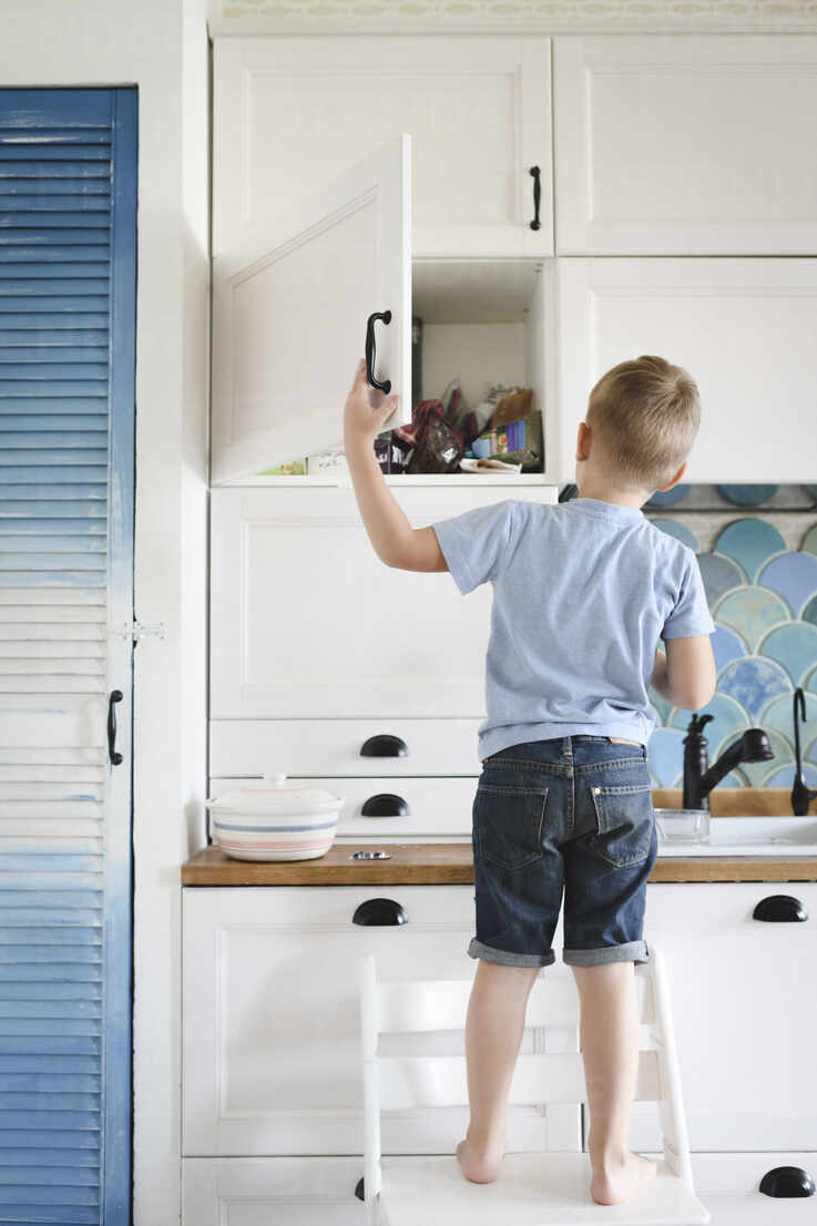 Back View Of Little Boy Standing On Chair In The Kitchen Looking Into Cupboard Stockphoto