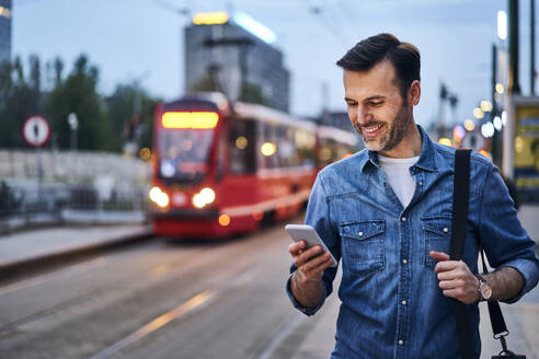 Man using smartphone while waiting for public tram in the evening - BSZF01082