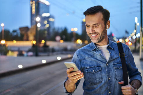 Man standing with smartphone waiting for evening commute after work - BSZF01085