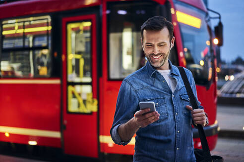 Smiling man using smartphone in the city with tram riding in background - BSZF01088