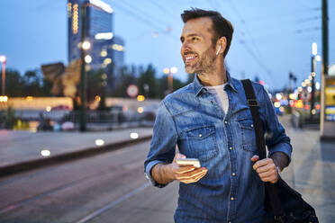 Smiling man using smartphone and listening to music through wireless headphones while waiting at tram stop during evening commute after work - BSZF01091