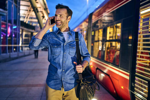 Man talking on phone in the city during evening with tram riding in background - BSZF01094