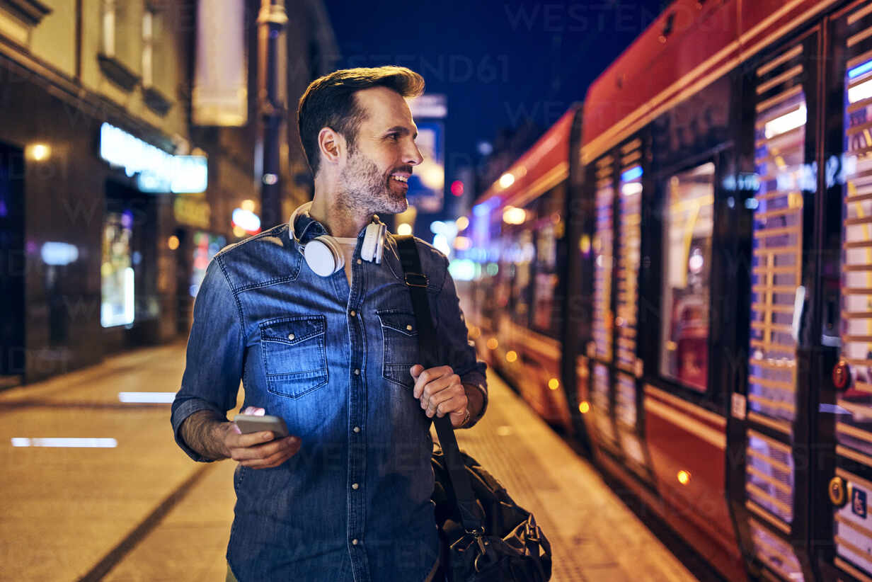 Smiling man using his smartphone in the city at night while waiting for the tram - BSZF01106 - Bartek Szewczyk/Westend61