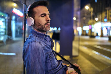 Man with wireless headphones snoozing while waiting for night bus in the city - BSZF01112