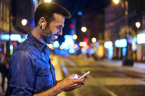 Man with wireless headphones using smartphone in the city at night - BSZF01115