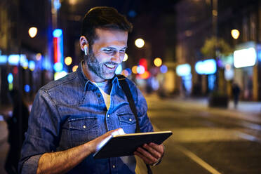 Smiling man with wireless headphones using digital tablet in the city at night - BSZF01118
