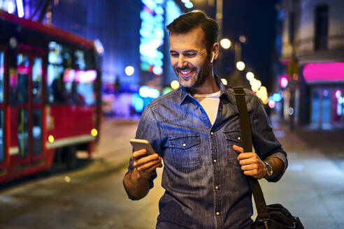 Smiling man with wireless headphones using smartphone while walking through the city at night - BSZF01121