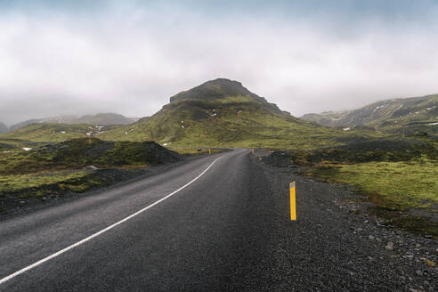 Iceland, South Iceland, Empty Solheimajokulsvegur road on cloudy day - TAMF01731