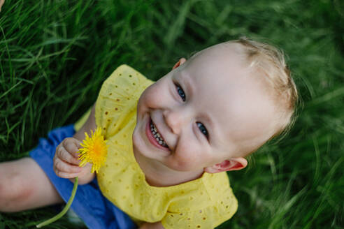 Portrait of happy little girl with dandelion sitting on a meadow - OGF00030