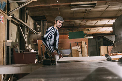 Carpenter at work with wooden board on a saw - VPIF01310
