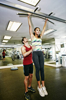 Woman working out with trainer in gymnasium - BLEF09500