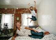Native American mother and daughter jumping on bed - BLEF09521