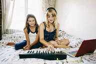 Sisters playing keyboard on bed - BLEF09524