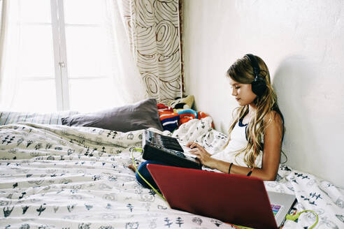 Native American girl recording music on bed - BLEF09527