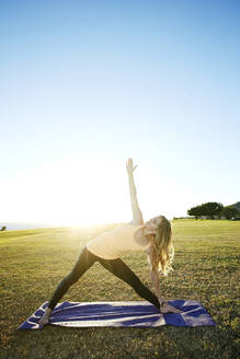 Caucasian woman practicing yoga in field - BLEF09557