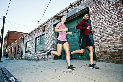 Caucasian couple jogging on sidewalk - BLEF09569