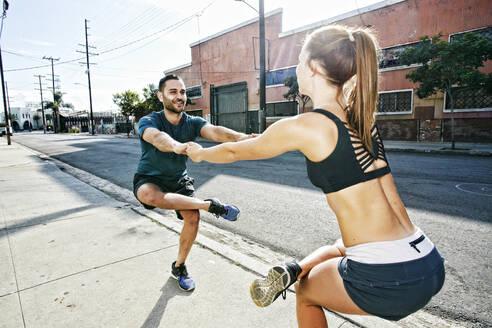 Caucasian athletes balancing on sidewalk - BLEF09575