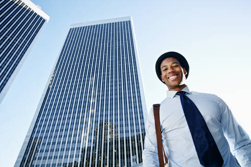 Black businessman smiling under highrise buildings - BLEF09602