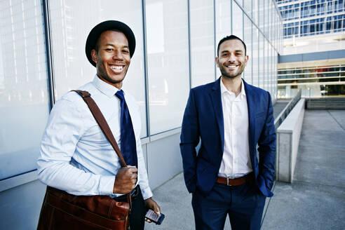 Businessmen smiling outside office building - BLEF09605