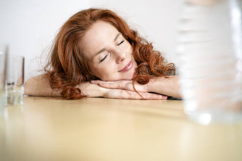 Redhead woman sleeping while leaning on table at home - DMOF00158
