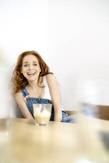Portrait of smiling woman sitting with drink at table against white wall in room - DMOF00164