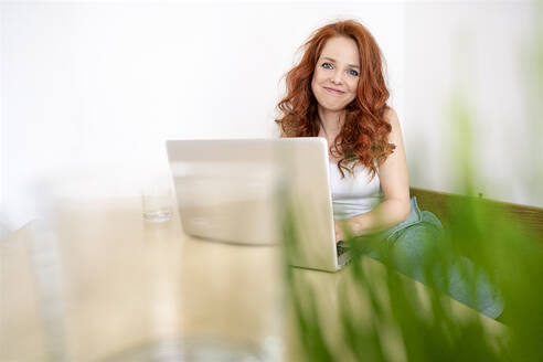 Portrait of smiling redhead woman sitting with laptop at table against white wall in room - DMOF00167