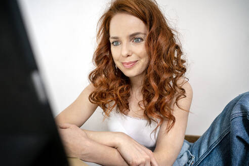Smiling redhead woman sitting with digital tablet against white wall in room - DMOF00170