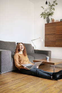 Full length of cheerful woman laughing while sitting with laptop in living room at home - DMOF00173