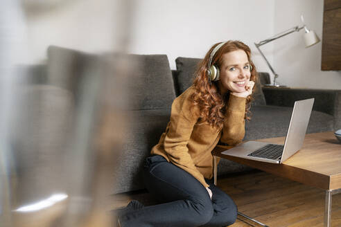 Portrait of beautiful woman wearing headphones while sitting by laptop on coffee table at home - DMOF00176
