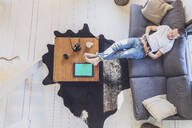 Directly above view of mid adult man relaxing while surfing net on digital tablet in living room at home - MMAF01083