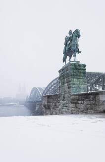 Kaiser Wilhelm I statue by Hohenzollern Bridge over Rhine river in city against sky during winter - GWF06135
