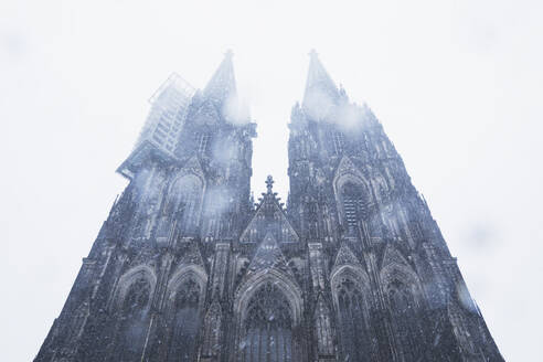 Low angle view of Cologne Cathedral in city during snowfall against sky - GWF06141