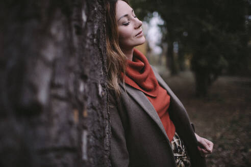 Portrait of woman with eyes closed leaning against tree trunk wearing turtleneck pullover - OGF00043