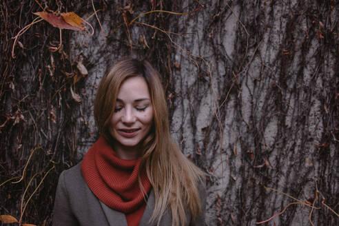 Deutschland, NRW, Köln, junge Frau stehend an der Wand mit Herbstblättern - OGF00052