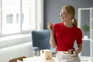 Happy young woman eating a piece of cake in office - JOSF03464