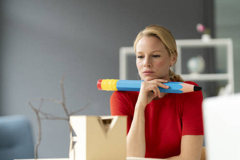 Young woman in office with oversized pen and architectural model on desk - JOSF03476