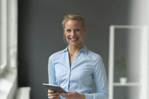 Portrait of smiling young businesswoman with tablet in office - JOSF03491