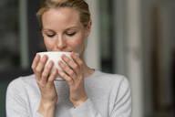 Young woman holding a coffee mug - JOSF03518